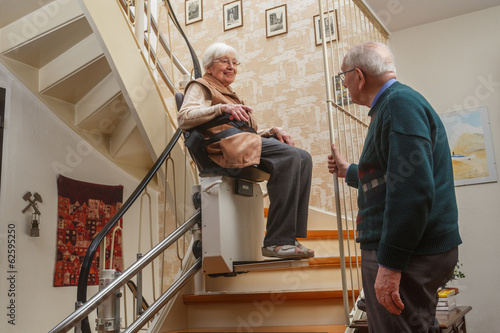 Leinwanddruck Bild elderly couple at the stairlift