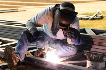 welder welding steel metal on construction site