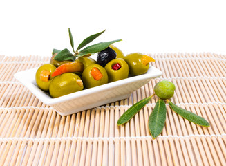 stuffed olives  with olive branch and leaves on a rustic mat bac