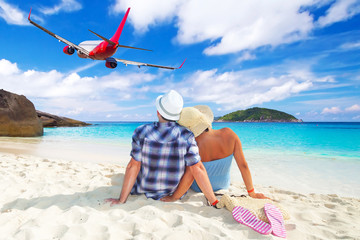 Couple in hug on the beach watching flying aircraft