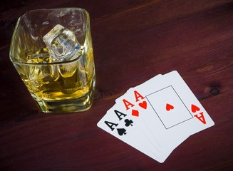 poker playing cards near wiskey glass