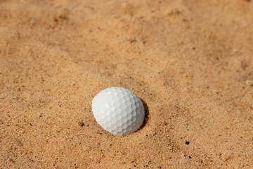 Golf ball in sand on bunker golf course