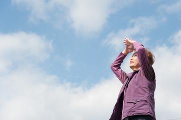 青空をバックに撮影した高齢者の女性