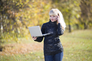 Beautiful young girl outdoors with laptop