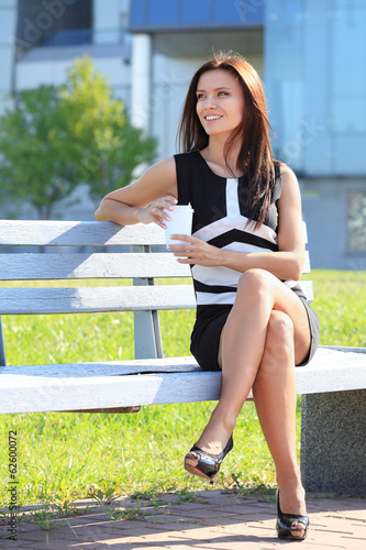 smiling young smart businesswoman having coffee break in office