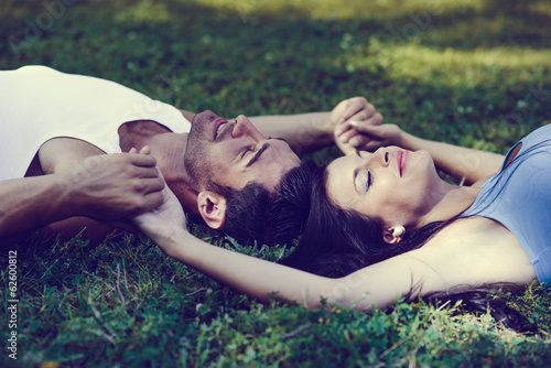 Happy smiling couple laying on green grass