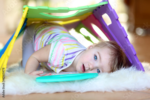 Happy little toddler girl playing hide and seek with puzzles