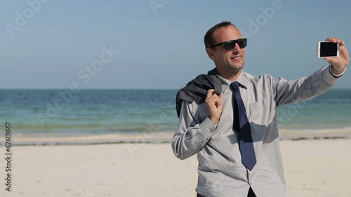Businessman taking selfie with smartphone on exotic beach