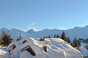 Snow-covered roofs in mountain landscape