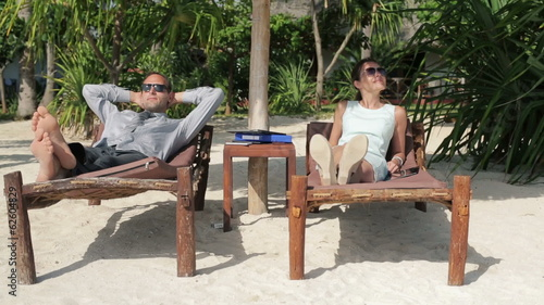 Business couple relaxing on sunbeds in exotic luxury resort
