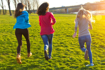 Three girls running in the park