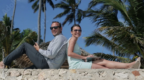 Happy business couple with tablet and laptop in exotic location