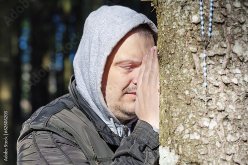 Religious man with a rosary near tree