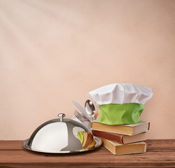 food tray, cap chef and cookbook on a beige vintage background