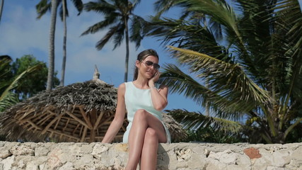 Beautiful businesswoman talking on cellphone in exotic location