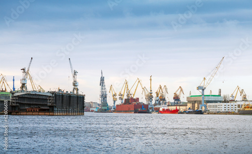 Industrial panorama with cranes and docks. Big Neva River