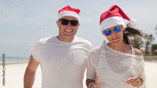 Funny happy couple fooling around in santa hats on the beach