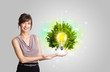 Young girl presenting idea light bulb with green tree