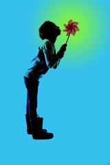 silhouette of a girl standing blowing a toy pinwheel blue backgr