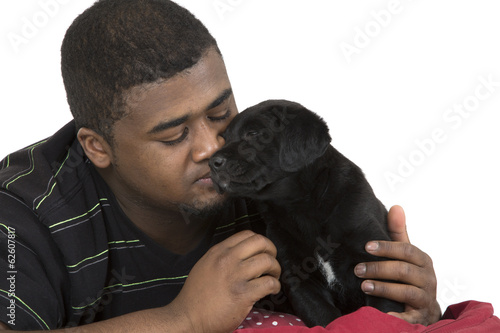 African American male model loving his black labrador puppy dog