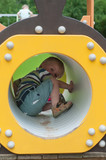 Young boy sitting in crawl tube