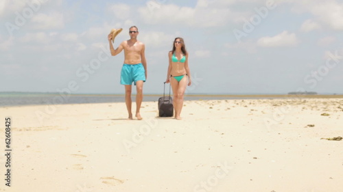 Couple with valise walking on beautiful exotic beach