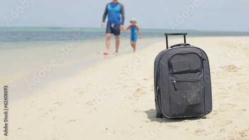 Father and son walking on exotic beach