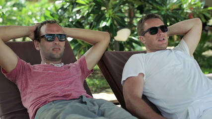 Two male friends talking and relaxing on sunbeds