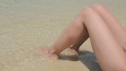 Young sexy woman feet in sea water on beach