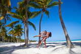 Man giving piggyback ride to girlfriend at the Caribbean beach