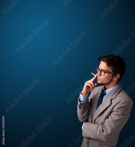 Young man smoking cigarette with copy space