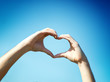 Hand heart shape against blue sky