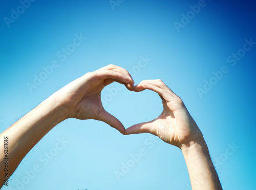 Hand heart shape against blue sky