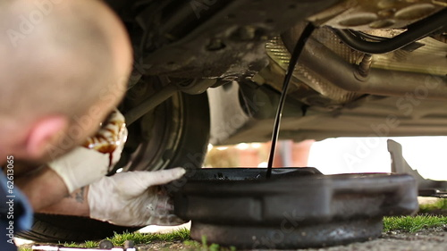 Car mechanic draining oil during a car service
