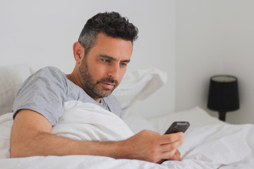 men in bed use his smartphone