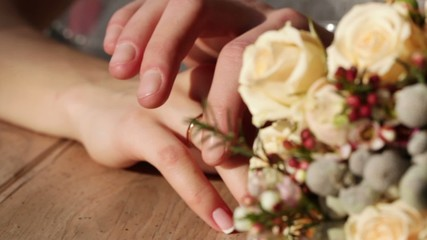 Hands next to wedding bouquet