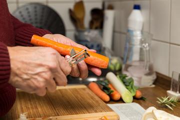 Rentner beim Gemüse schälen