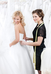Shop assistant helps to the bride to put the wedding dress on