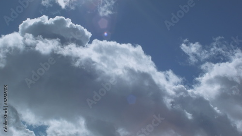 Timelapse view, clouds in front of blue sky, with lens flare