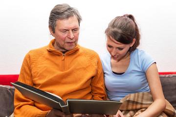Vater und Tochter sehen sich gemeinsam Bilder an
