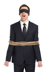 Portrait of blind-folded businessman tied with the rope