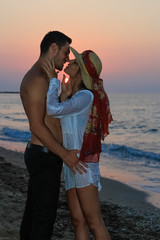 Happy young couple kissing at the beach at dusk.
