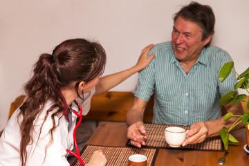 Altenpflegerin beim Kaffeetrinken mit Senior