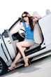 Pretty woman in sunglasses sits in the white car