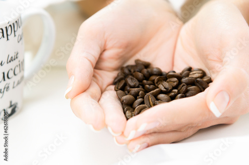 Womans Hands full of roasted coffe beans shaped as heart