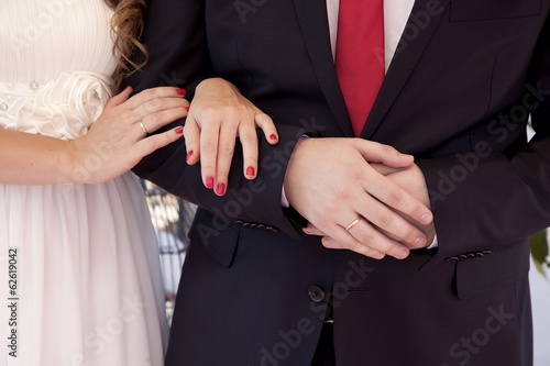hands of newlyweds gently holding each other