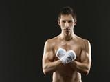 Fototapeta Half-length portrait of exercising boxer