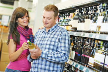 Family choosing wine in supermarket
