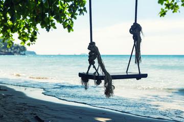 Swings at sea coast against water and sky