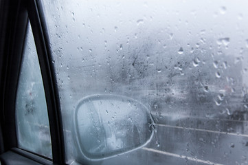 View of a car side mirror from inside the car with condensation